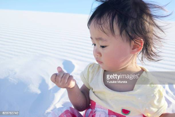 A little girl playing on sand dune