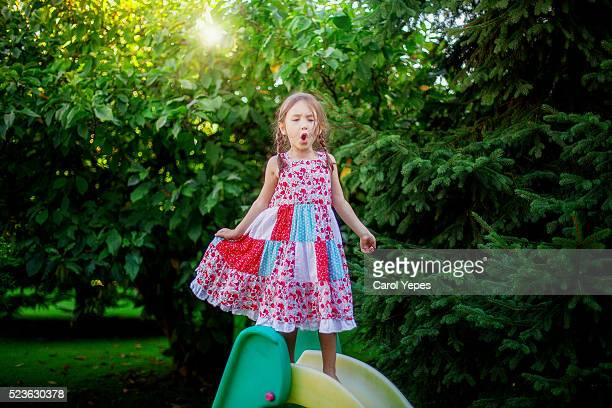 little girl playing on slide and singing