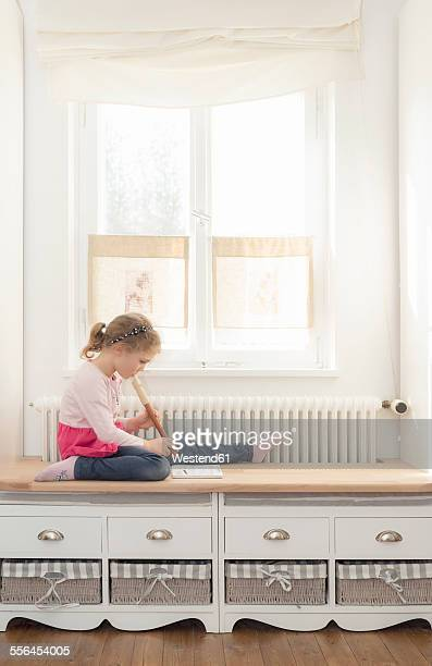 Little girl playing recorder at home