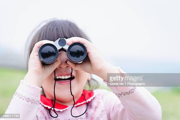 Little girl playing telescope.