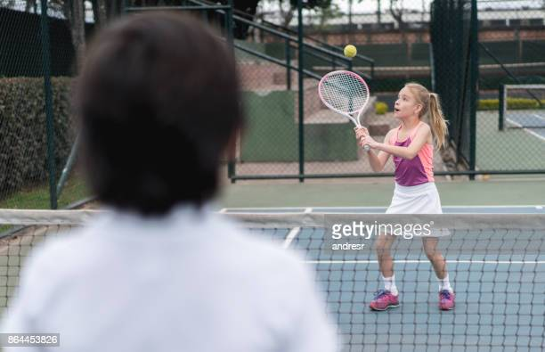 Little girl playing tennis outdoors with a friend