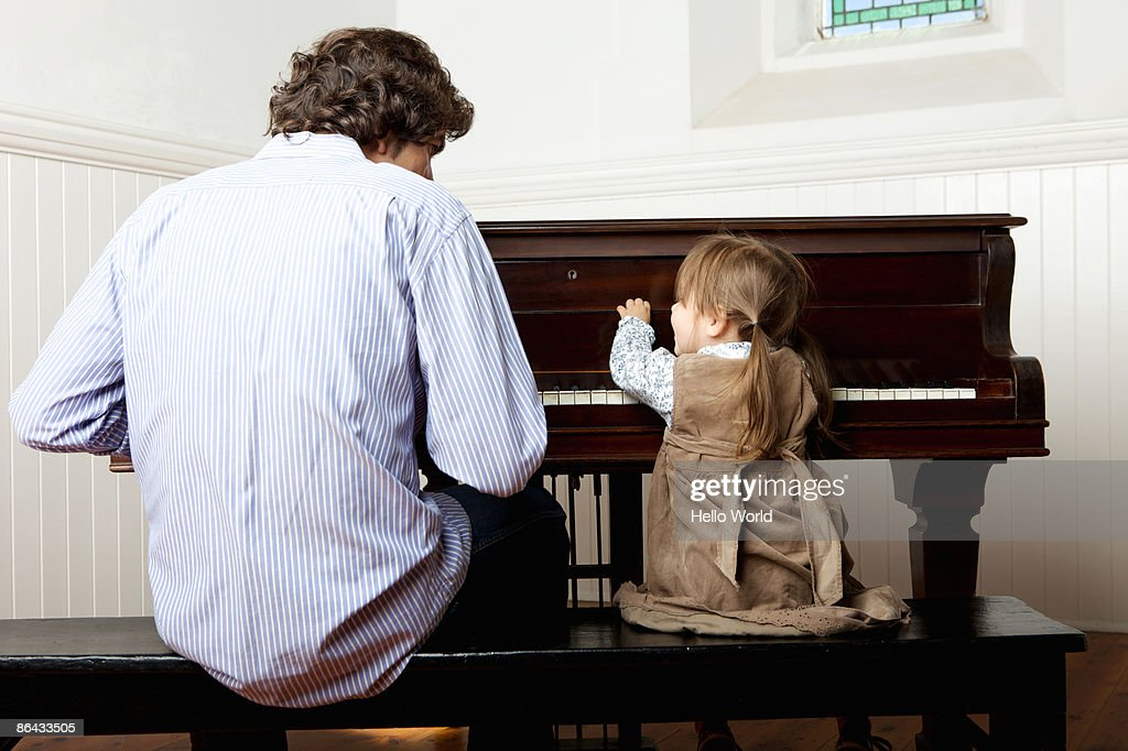 little girl playing the piano with father : Stock Photo