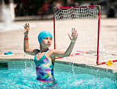 Little girl aged 9 playing water polo in outdoors swimming pool. Sunny summer day on mallorca.