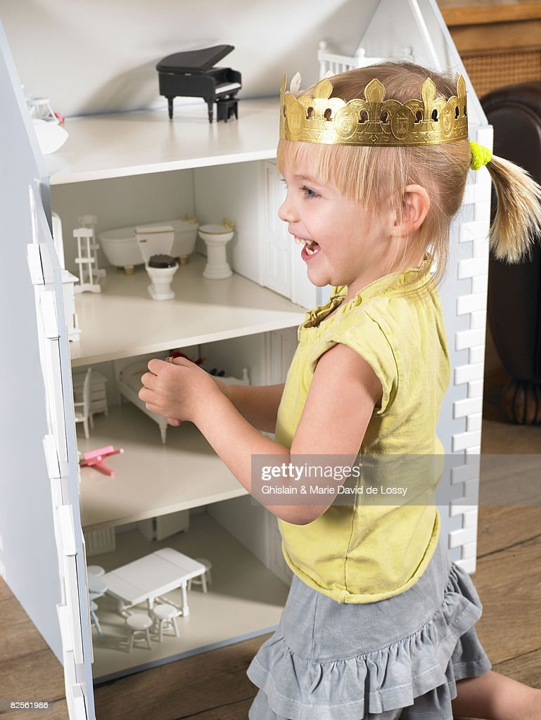 Little girl playing with a doll house : Stock Photo