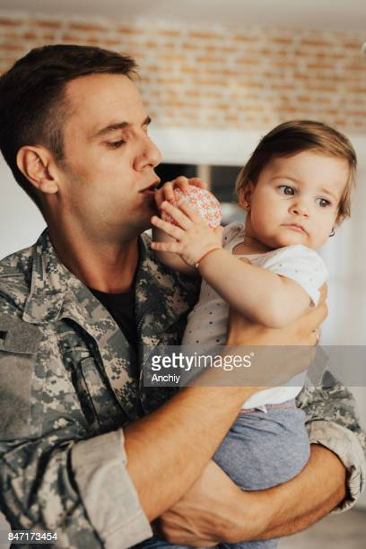 Little girl playing with ball, while her dad holds her in his arms