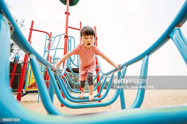 Little girl playing with climbing equipment