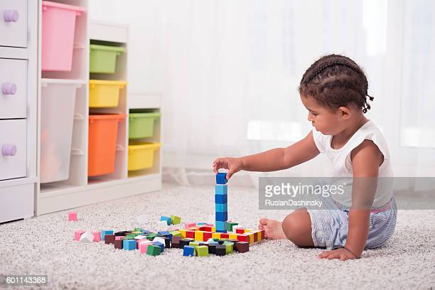 Little girl playing with cubes.