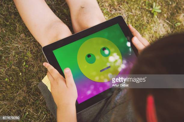 Little girl playing with digital tablet and colorful emoticon displayed on the screen taken from above.