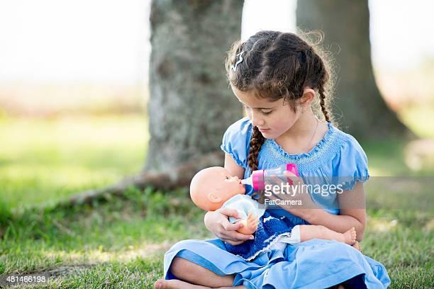 Kleines Mädchen spielt mit Puppen im Park