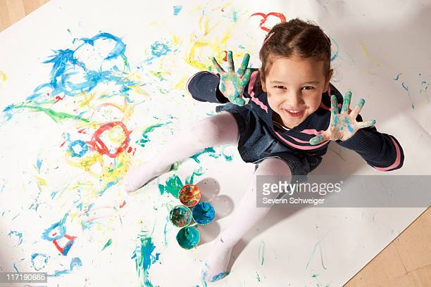Little girl playing with finger paint