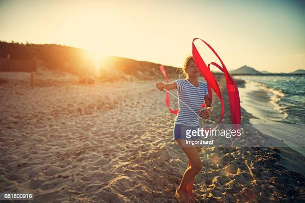 Little girl playing with gymnastics ribbon on the beach.