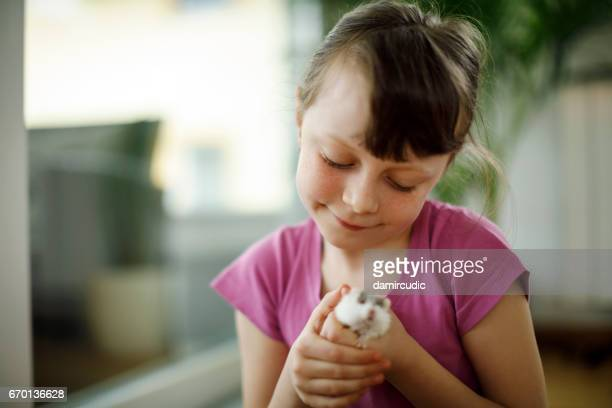 Little girl playing with hamster