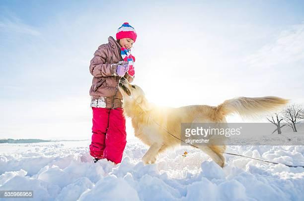 Kleine Mädchen spielen mit Ihrem Hund im Schnee.