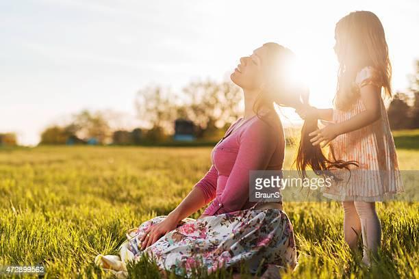 Menina brincando com sua mãe de cabelo durante a Primavera dia.