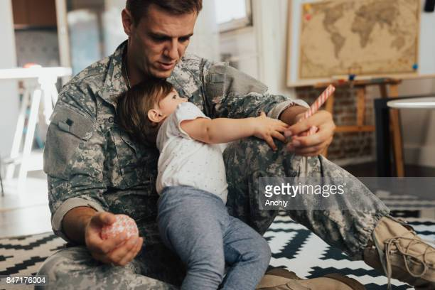 Little girl playing with her soldier daddy