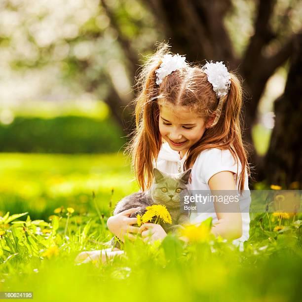 Kleine Mädchen spielen mit Kätzchen auf Rasen im park