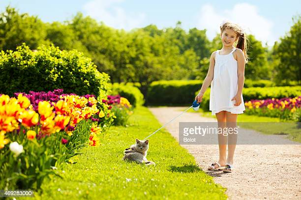 Little girl playing with kitten on lawn in park