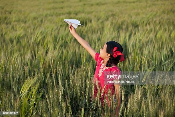 Little girl playing with paper plane in field