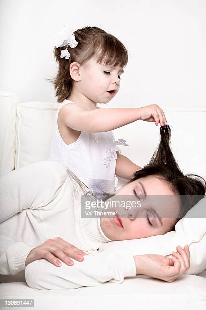 Little girl playing with the hair of her sleeping mother