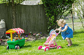 Little girl (12-23 months) playing with toy stroller in garden
