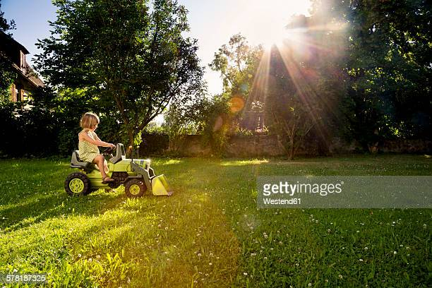 Little girl playing with toy tractor in a garden