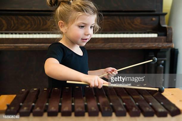 Kleines Mädchen spielen Xylophon mit Pianomusik im Hintergrund, horizontale.