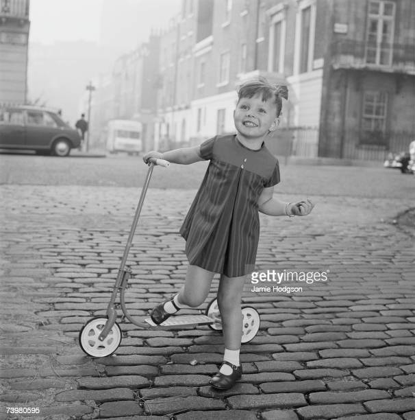 A little girl plays with her scooter on a cobbled street circa 1965