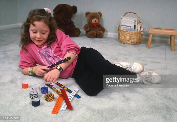 A little girl plays with her 'slap wrap bracelets' December 7 1990 in New York City The bracelets are made of flexible stainless steel sealed with a...