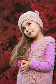 Little girl portrait in hat at autumn clothes against red tree foliage background, she looks up with a cunning look