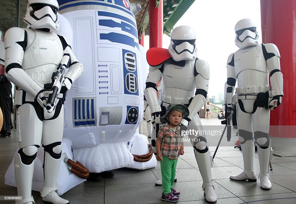 A little girl poses for a photo with Star Wars fans during the annual Star Wars Day in Taipei on May 4, 2016. Some 100 star wars fans dress the different costumes during a cosplay event to mark the annual Star War Day. / AFP / SAM YEH