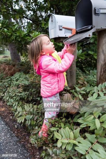 Little girl posing near a mailbox
