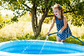 Little girl pouring water into a small pool