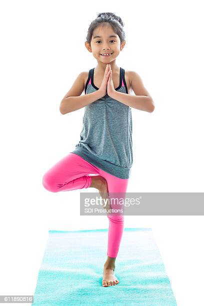 Little girl practices tree pose in yoga class