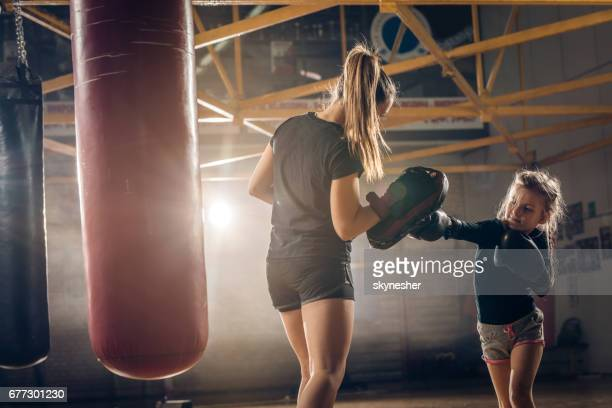 Little girl practicing boxing with her coach in health club.