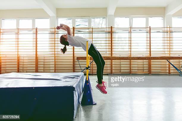 Fillette pratiquant le saut en hauteur.
