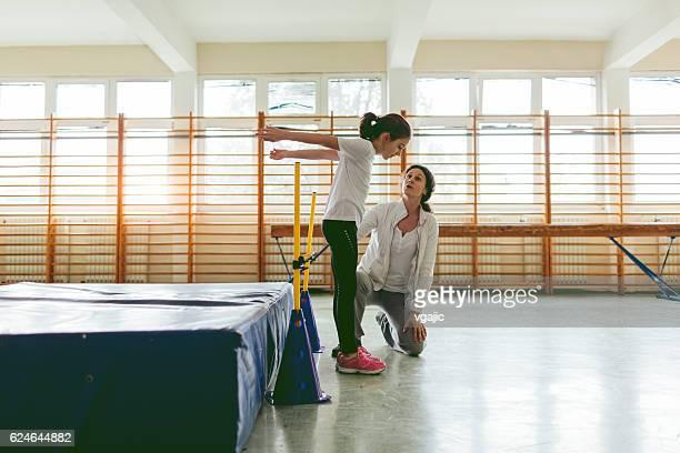 Kleines Mädchen üben Hochsprung mit Ihrem Trainer.