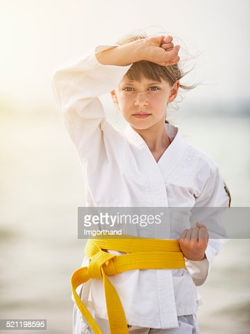 Little girl practicing karate on the beach
