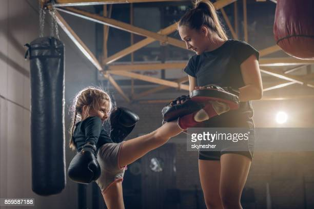 Little girl practicing kick boxing with female coach.