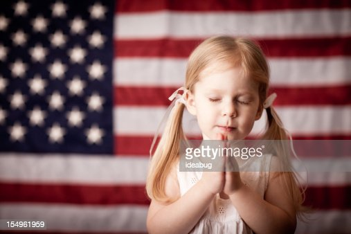 Little Girl Praying in Front of American Flag