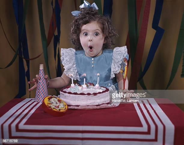 A little girl prepares to blow out the three candles on her birthday cake 1950