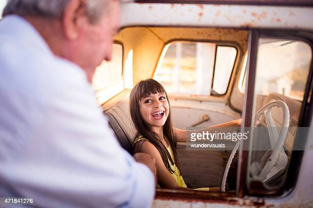 Little girl pretending to drive her grandpa's old vehicle
