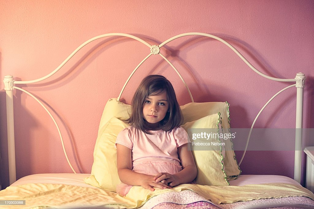 little girl propped up by pillows in her bed stock photo getty images
