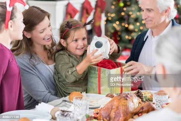 Meisje trekt cadeau uit doos op kerstdiner
