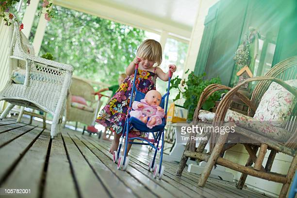 Little girl pushing doll in stroller