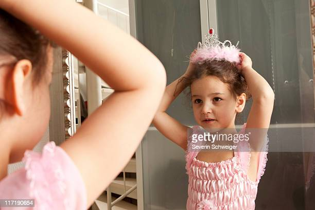 Little girl putting crown on her head