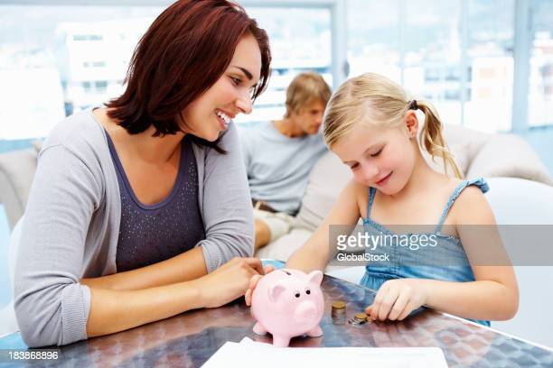 Little girl putting money in piggy bank with her parents