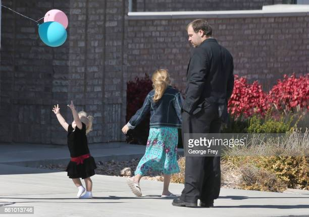 A little girl reaches for a balloon as she plays outside the chapel of the Church of Jesus Christ of LatterDay Saints during the funeral of Heather...