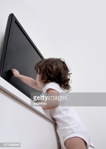 Little girl reaching up to touch the TV