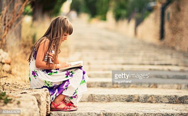 Little girl reading a book on stairs.