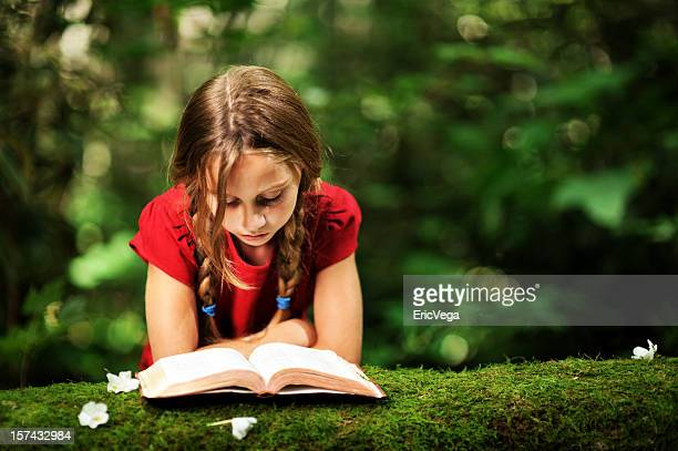 Little girl reading a book under a tree